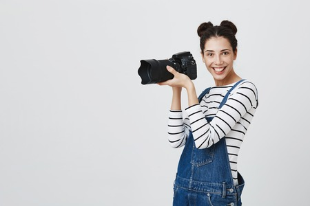 Waist-up portrait of excited young pretty european girl photographer with two hairbuns wearing striped top using modern camera, looking with broad smile at camera, being happy to do her work Stock Photo