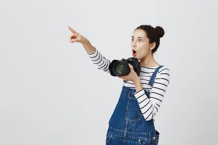 Joyful hipster girl with hairbuns in trendy clothing walking around during excursion, watching local curiosities: pretty girl taking pics using camera and pointing with index finger in excitement Stock Photo