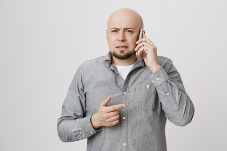 Portrait of charming bald man with beard talking on smartphone and expressing confusion or perplexity, pointing right with index finger and standing over gray background.