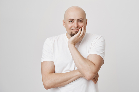 Indoor portrait of happy smiling bald european man holding head on hand, wearing white t-shirt and being touched or pleased with something he sees, standing over gray background.