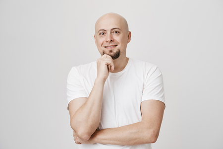 Portrait of handsome bald european male touching his beard while smiling and thinking about something with crossed hand, wearing white t-shirt and standing over gray background. Stock Photo