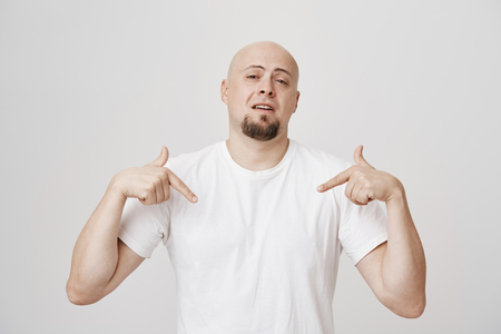 Portrait of smug and confident bald caucasian man pointing down while wearing white t-shirt and standing over gray background. Guy assures woman that he will show her heaven once they reach bedroom