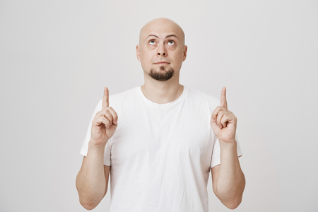 Studio portrait of attractive bald bearded man who points up with both index fingers while looking there with lifted eyebrows, standing against gray background. Model directs at advertisement