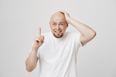 Portrait of funny bald european male with beard holding hand on head while pointing up with another, smiling and recalling something over gray background. Man finally remembered what he forgot Stock Photo