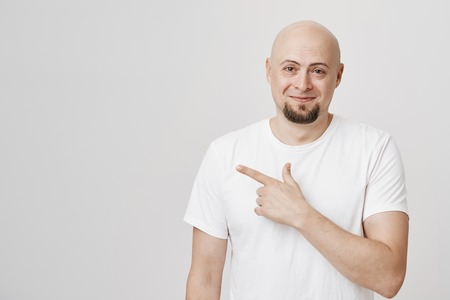 Indoor shot of handsome bald european man with beard, wearing white t-shirt and pointing left and smiling broadly over gray background. Guy points at his twin-brother as someone mistaken Banco de Imagens
