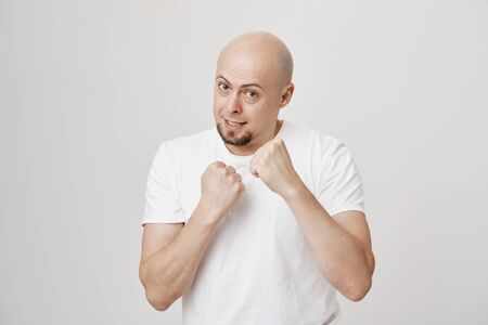 Studio portrait of mature bald man with beard standing in boxer pose with raised fists as if defending or fighting, expressing confidence and readiness, standing over gray background in white t-shirt.