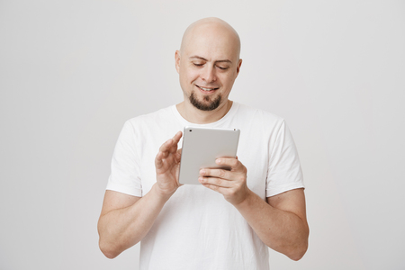 Pleased mature bald man with beard browsing through tablet or messaging, standing over gray background. Successful businessman checks with his notes in gadget to decide what he needs to buy Stock Photo