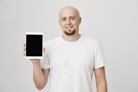 Portrait of adult bald man with beard smiling cheerfully and showing tablet at camera, standing against gray background. Husband makes present for his wife on valentine day. Stock Photo