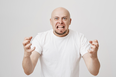 Angry and insane bald bearded guy expressing his readiness to kill somebody, being filled with anger and negative emotions, standing over gray background and gesturing. Employer is mad
