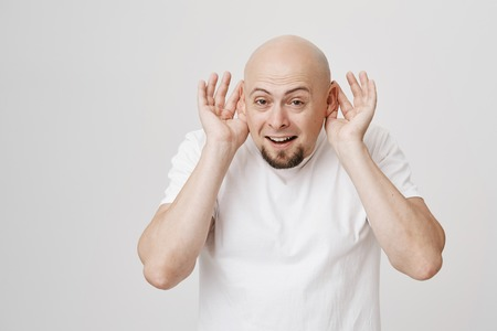 Funny and tricky bald man with beard holding ears with hands as if perking it, or wanting to hear better, standing over gray background. I am ready to listen. Guy loves spreading and hearing rumors