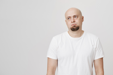 Portrait of bored and tired bald man with beard looking aside with gloomy expression, standing over gray background. Guy hates do house chores but he has strict wife. Office clerk stands in huge queue Stock Photo