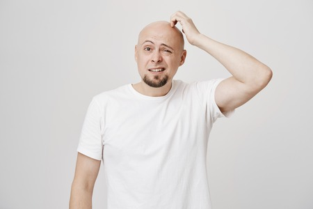 Portrait of confused bald caucasian male model with stupid expression, scratching head and looking aside not having any clue, standing over gray background. Man forgot something but do not know what