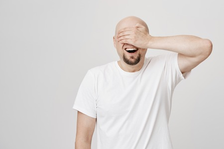 Astonished and excited bald bearded man with broad smile covering eyes with hand and awaiting for something positive to happen, standing over gray background. Birthday guy waits for his present
