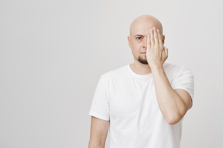 Calm and serious bald man with beard covering half of face with hand, wearing white t-shirt and standing against gray background. Masks and emotions concept. Sometimes you have to hide true feelings