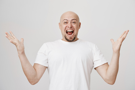 Studio portrait of overwhelmed and excited bald caucasian man with beard shouting of happiness and spreading hands, showing his joy because of success over gray background. Guy became father