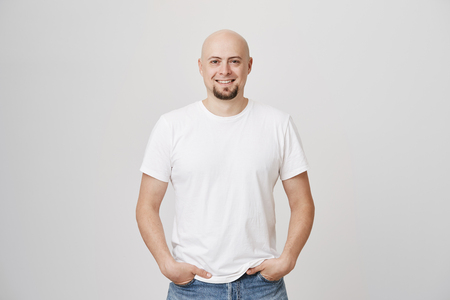 Indoor shot of bald european guy with pretty beard holding hands in pockets while smiling confidently and standing over gray background. Founder of company just reached top of sales Stock Photo