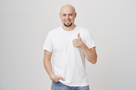 Self-assured and successful bald caucasian man holding hand in pocket and showing positive answer with thumbs up, smiling broadly and standing over gray background. I approve your choice, son