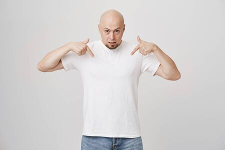 Portrait of displeased bald european adult pointing down and expressing disappointment, standing against gray background. Model showing copy space, being mad or annoyed with something Archivio Fotografico