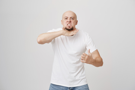 Portrait of angry annoyed bald man with beard gesturing as if cutting neck, showing that he is fed up and quit, standing over gray background. I am sick and tired of this job. Enough of this bullshit