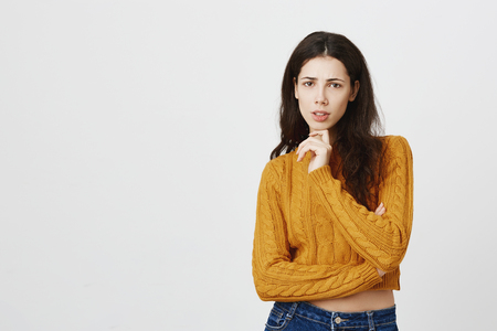 Portrait of attractive european female in yellow cropped sweater holding finger in ching while expressing dislike and being puzzled while thinking or discussing something, over gray background.