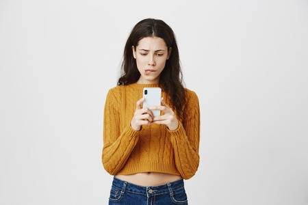 Portrait of anxious and puzzled cute european girl holding smartphone and looking at screen while biting lip and being worried, standing over gray background. Woman forwarded message to the same guy