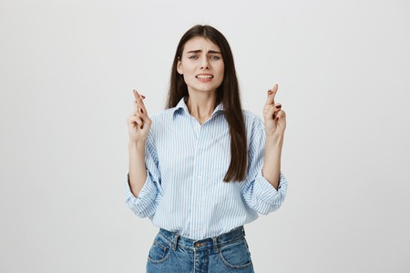 Studio portrait of charming female model standing with raised crossed fingers wishing something badly while standing over gray background. Student hopes not to be called out to blackboard.