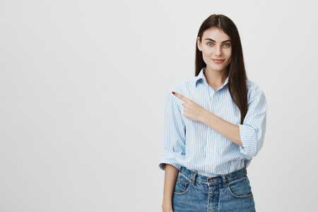 Beautiful and tender girl pointing left with forefinger, wearing casual shirt and jeans and standing over gray background. Model advertises product and shows it on copy space. Stock fotó