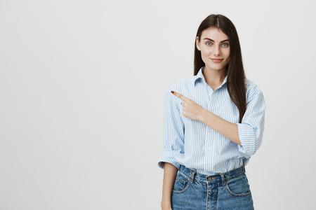 Muchacha hermosa y blanda que señala a la izquierda con el índice, vistiendo camisa casual y pantalones vaqueros y de pie sobre fondo gris. El modelo anuncia el producto y lo muestra en el espacio de la copia.