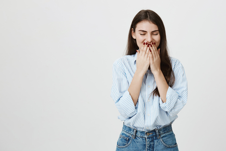 Indoor shot of attractive positive woman smiling broadly and feeling happiness, covering her mouth while standing over gray background. Girl is embarrassed after kiss of handsome guy Archivio Fotografico