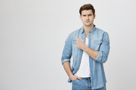 Serious looking handsome student in denim clothes squinting at camera and pointing left with index finger while standing against gray background. Guy asks quesion being uncertain if it is true