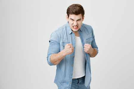 Furious muscular european male model in denim shirt with trendy haircut holding fists in front of him as if ready for fight or challenge, clenches teeth, having angry and aggerssive expression