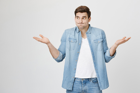 Portrait of funny handsome guy, shrugging and spreading hands, expressing unknowladge and confusion, widen eyes, standing over gray background. I do not know what are you talking about