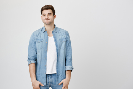 Perplexed and puzzled handsome guy, standing straight in denim clothes, puffing cheeks and starring at camera, over gray background. Son after huge party do not know how to clean all mess. Stock Photo