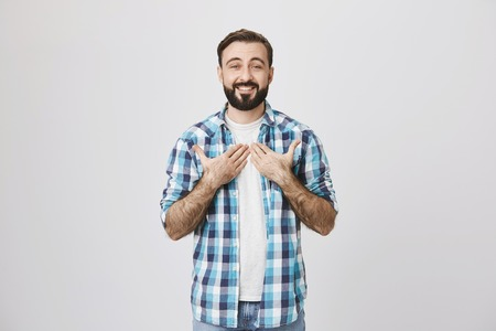 Portrait of attractive caucasian bearded man pointing at his chest while smiling broadly over gray background. Believe me please. Person is moved almost to tears because of some good event Stock Photo