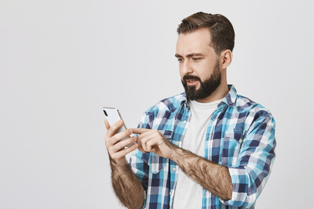 Portrait of attractive guy with beard and moustache holding smartphone and browsing network with surprised and perplexed expression, standing against gray background. Husband just got anxious message Banco de Imagens