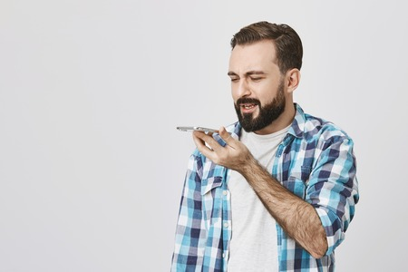 Studio portrait of adult bearded male model holding smartphone near mouth while speaking in it with puzzled expression. Guy bought new phone and turned on speaker by accident