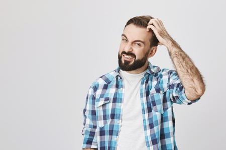Studio shot of mad bearded male roughly scretching his head and expressing confusion, over gray background. Husband has problems with dandruff, he thinks about buying new shampoo