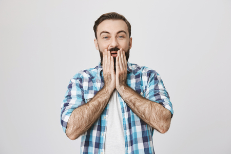 Indoor shot of european male with beard and moustache, holding both hands on face, expressing surprise and pleasant shock, standing over gray background. He laughs over friend who slept on banana peel