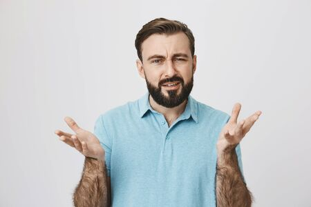 Attractive adult man with beard and moustache, raising hands in frustrated gesture feeling unsure in something, standing over gray background. What are you talking about, I can not figure it out 版權商用圖片