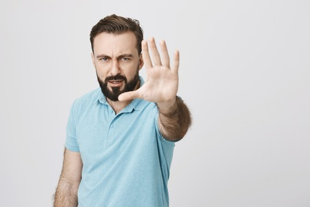 Man with a beard and moustache showing stop gesture with an angry look. Guy with serious expression says to his daughter that she would not come anywhere because girl is grounded.