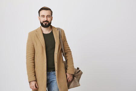 Indoor portrait of attractive businessman in coat and casual clothes, holding bag on shoulder and smiling at camera, over gray background. Man talks to his neighbor in corridor Stock Photo