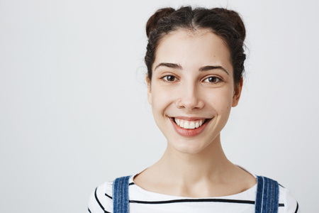 Close-up portrait of attractive young european woman with bright smile, two buns hairstyle and pierced nose, standing over gray background. Girl decided to change her appearance cardinally Stock Photo - 95314468