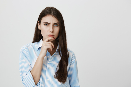 Indoor portrait of attractive european model holding hand near chin staring at camera with frowned eyebrows and serious face, expressing disbelief over gray background. Girl thinks boyfriend lies