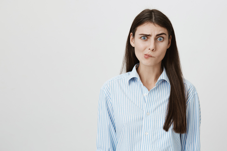 Perplexed and confused woman with questioned expression standing over gray background having no clue what to do next. Foreigner asking her something but she can not understand his language Stock Photo