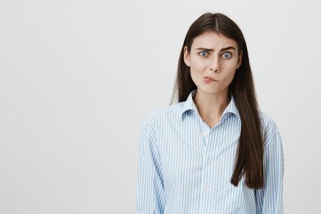 Verblüffte und verwirrte Frau mit dem fragenden Ausdruck, der über dem grauen Hintergrund steht, der keine Ahnung hat, was als Nächstes zu tun ist. Ausländer fragen sie etwas, aber sie kann seine Sprache nicht verstehen