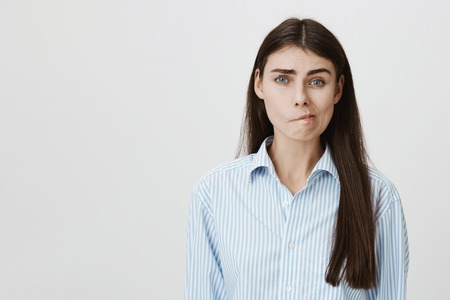 Portrait of european woman with perplexed and gloomy epxresion standing over gray background in blue-collar shirt. Wife weighing options while thinking about bills and from who she can loan
