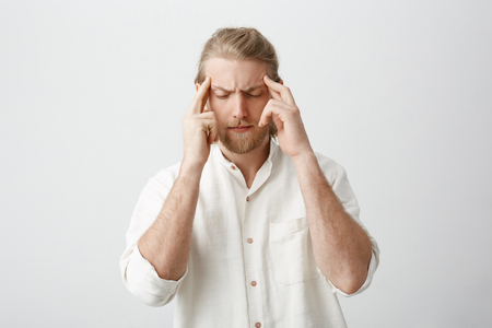 Tired determined handsome blond male with beard and moustache, holding fingers on temples, frowning, feeling pain or trying to focus, standing over gray background. Guy tries to work while it is loud