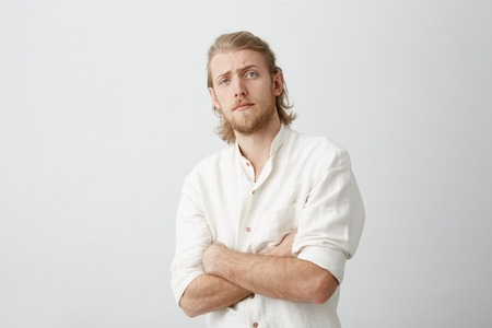 Portrait of doubtful attractive blond bearded man bending backwards, standing with crossed hands, lifting eyebrows and looking with disbelief over gray background. Guy do not believe tv reporters