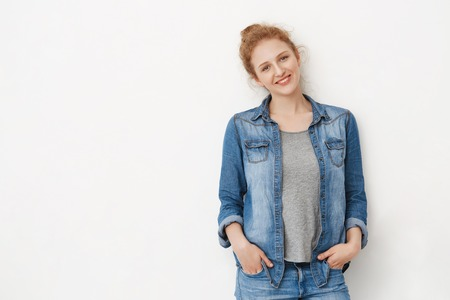 Beautiful caucasian redhead with blue eyes, leaning on gray background while holding hands in jeans, smiling and looking happily at camera. Girl waits for her neighbour to go shopping together