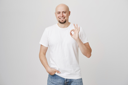 Portrait of confident good-looking bald bearded caucasian guy showing okay or fine gesture while holding hand in pocket, smiling broadly at camera and standing over gray background. Stock Photo